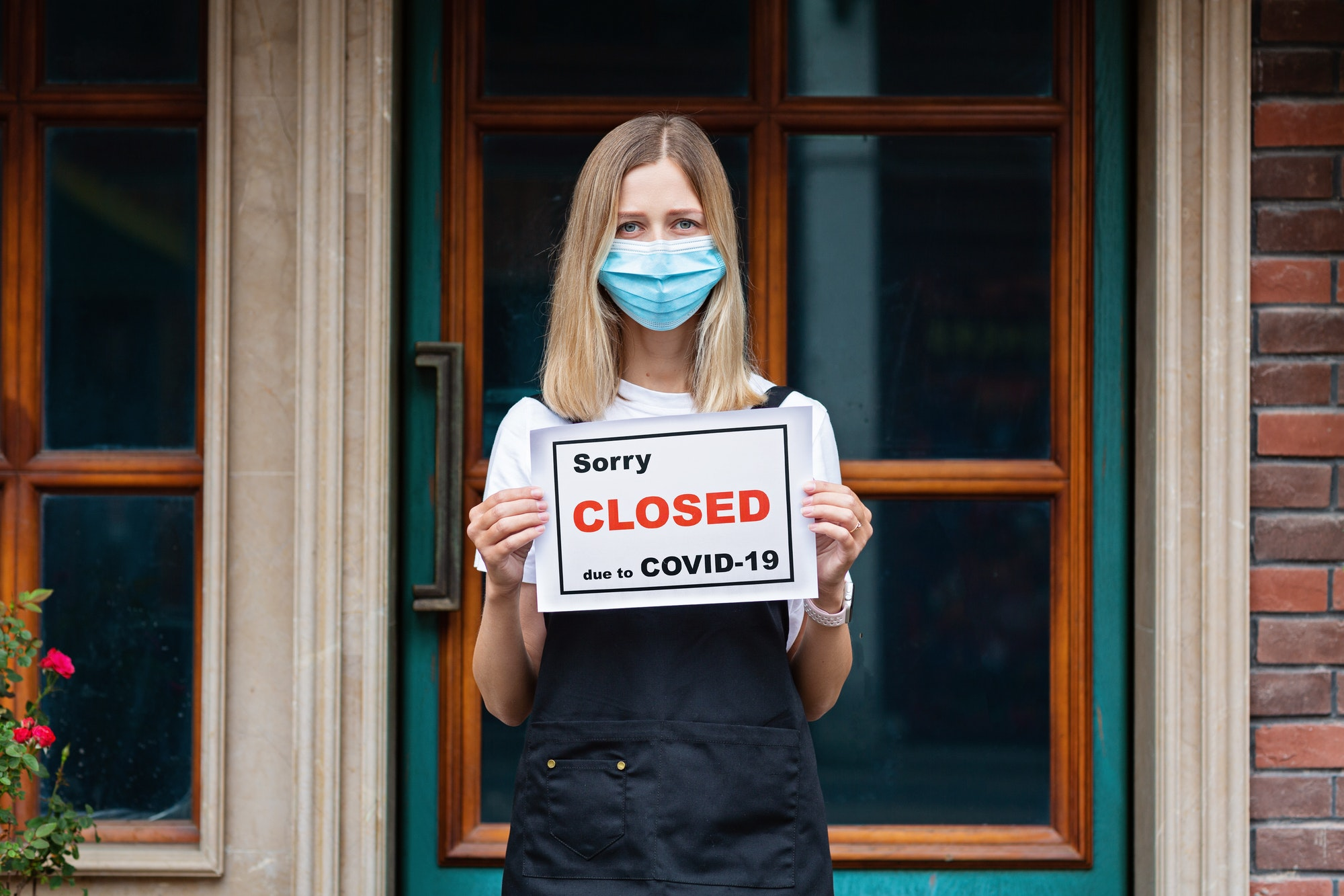Restaurant owner holding note sorry closed due to covid19. Shutdown coronavirus quarantine
