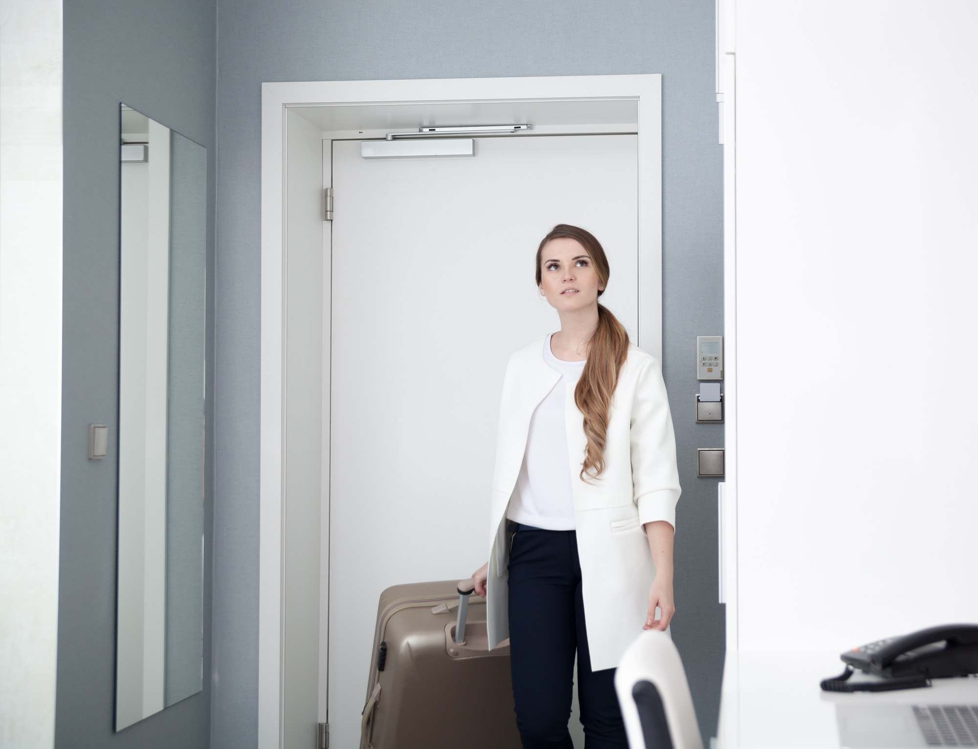 Woman pulling suitcase in modern hotel room