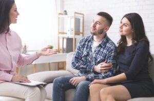 Young spouses listening to specialist at family consultation