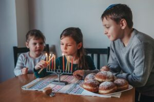 Sister girls and brother family lighting candles on menorah for traditional Jewish Hanukkah holiday