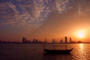 An old ship with Bahrain's flag in front of the city and the sunset