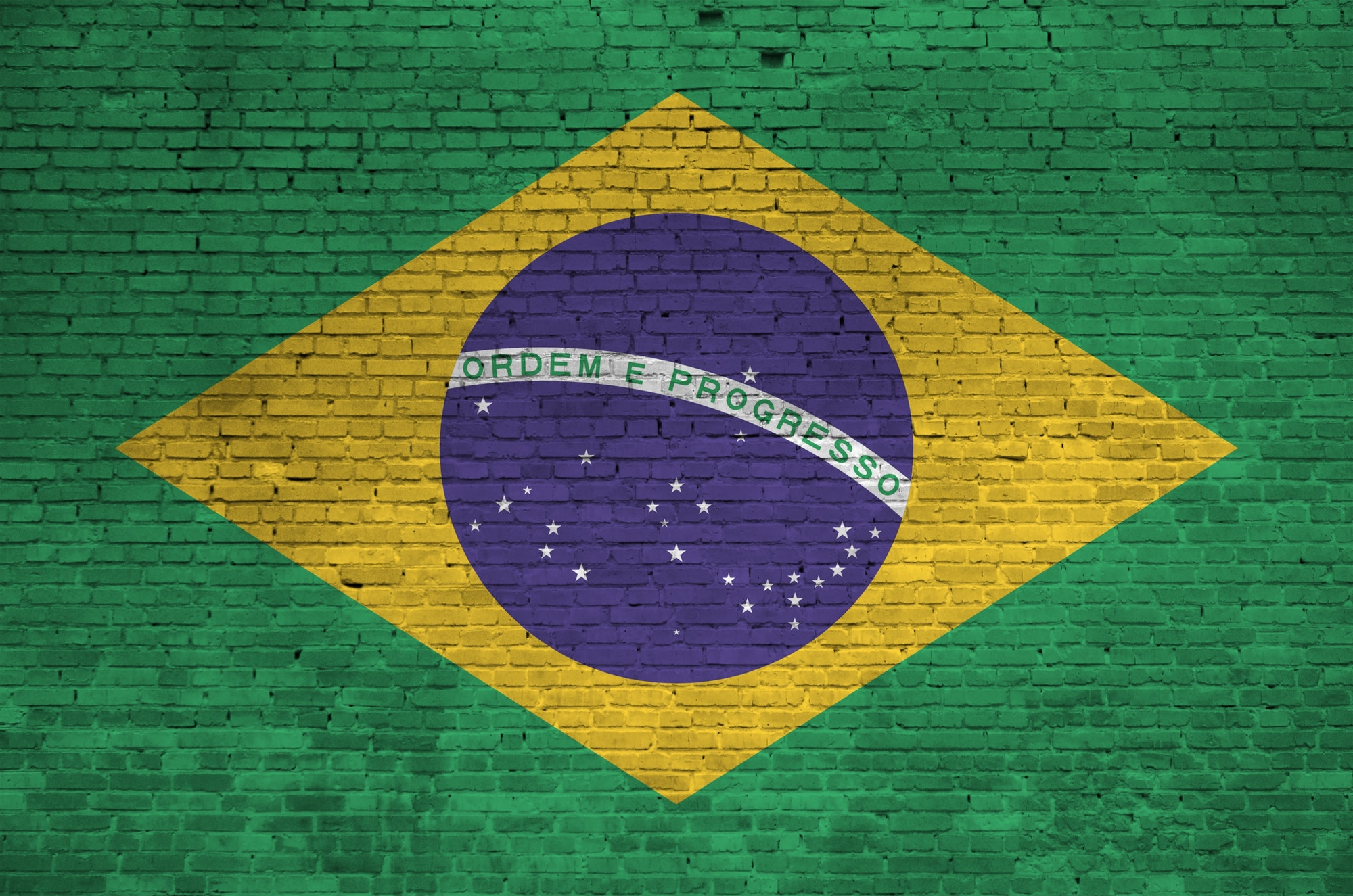 Brazil flag depicted in paint colors on old brick wall close up