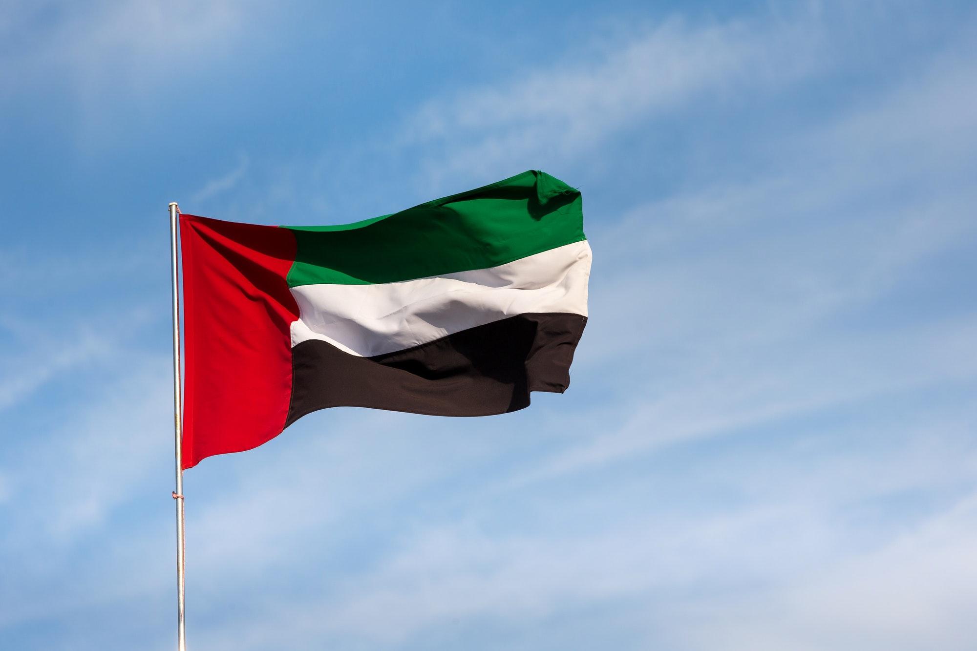 UAE flag waving in the sky, national symbol of UAE. UAE National day. UAE flag day.